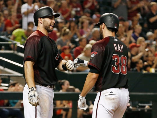 Arizona Diamondbacks' Robbie Ray (38) celebrates after scoring against the Philadelphia Phillies, with Paul Goldschmidt, left, during the fifth inning of a baseball game Saturday, June 24, 2017, in Phoenix. (AP Photo/Ross D. Franklin)