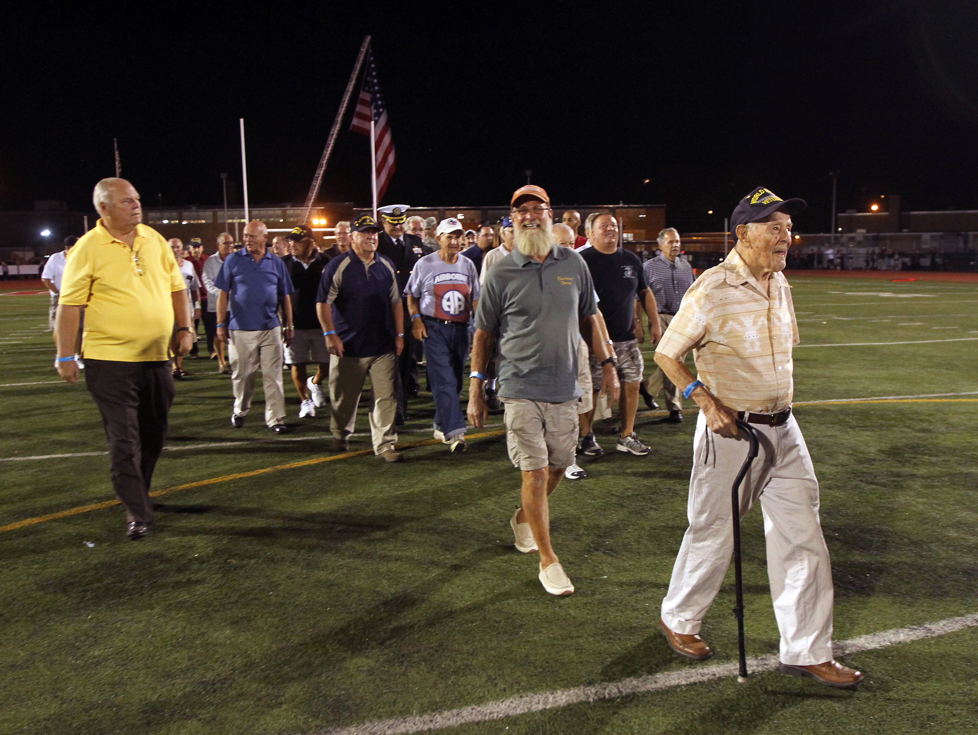 98-year-old World War II Air Force Veteran Steve Bolcar, r, leads a group of Veterans on the Boonton High football field as the school honored its graduate military veterans during halftime of the Boonton High School football game Friday night. The vets, some of whom are still residents, others coming back from out of town, also enjoyed a tailgate party prior to the game and ceremony. September 18, 2015, Boonton, NJ.