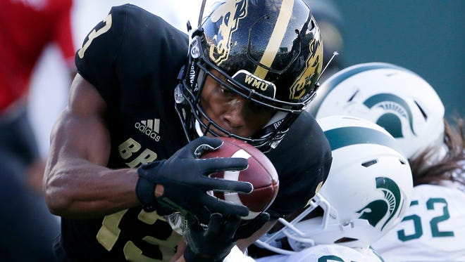Wide receiver Keishawn Watson (13) of the Western Michigan Broncos is tackled by safety Khari Willis (27) of the Michigan State Spartans after making a first down during the fourth quarter at Spartan Stadium on September 9, 2017 in East Lansing, Michigan. Michigan State defeated Western Michigan 24-14.