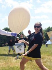 Abby DiNardo shows off a high altitude balloon and cube that was launched late last month and took photos at nearly 110,000 feet.