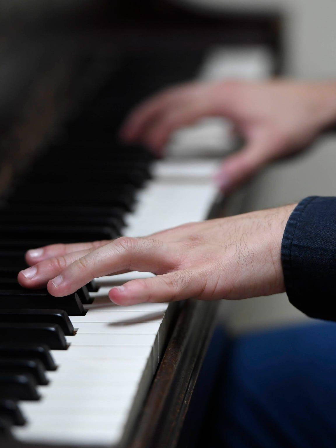 Fingers on the keys, Brazilian musician Rafael Pereida rehearses after work at the University of Evansville's Krannert Hall of Fine Arts Thursday, May 25, 2017.