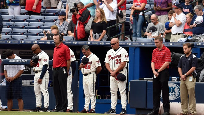 Atlanta Braves manager Fredi Gonzalez  and fans and coaches observe a moment of silence before Sunday's game, honoring a fan who fell to his death Saturday night at Turner Field.