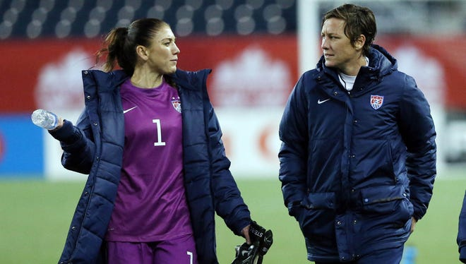 Hope Solo talks with teammate Abby Wambach after a friendly vs. Canada in 2014.