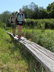 Top: Megan Kidston and Ryley Breiddak walk along wetlands