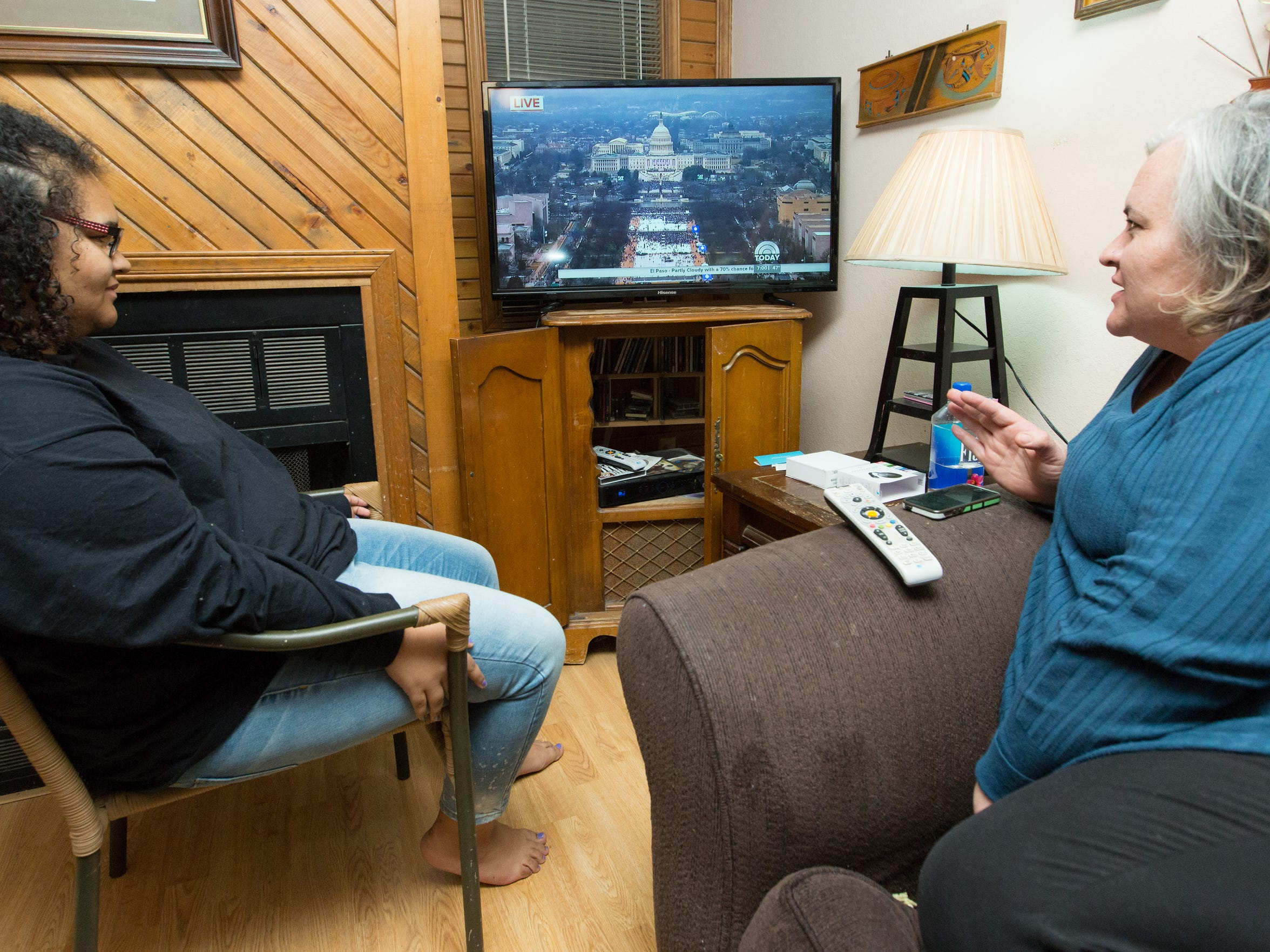 """Sarah Stevens, right, and her daughter Quinlan Pope, 16, watch a recording of Donald Trump's  inauguration on Monday, Jan. 23, 2017. Stevens says that she disagrees with Trump morally on most every issue, """"It sickens me to even watch this,"""" said Stevens."""