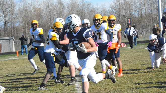 Sault High running back John Robinson (5) follows the line on a clear path to the end zone during a playoff game against Saginaw Arthur Hill Saturday. The Blue Devils won 60-6