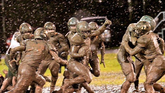 Grant Fountain of Cedarville runs the ball through the mud while Louie Mayer of Rudyard (33) pursues in last week's regular season finale at Rudyard. The Trojans and Bulldogs both open the playoffs Thursday night.