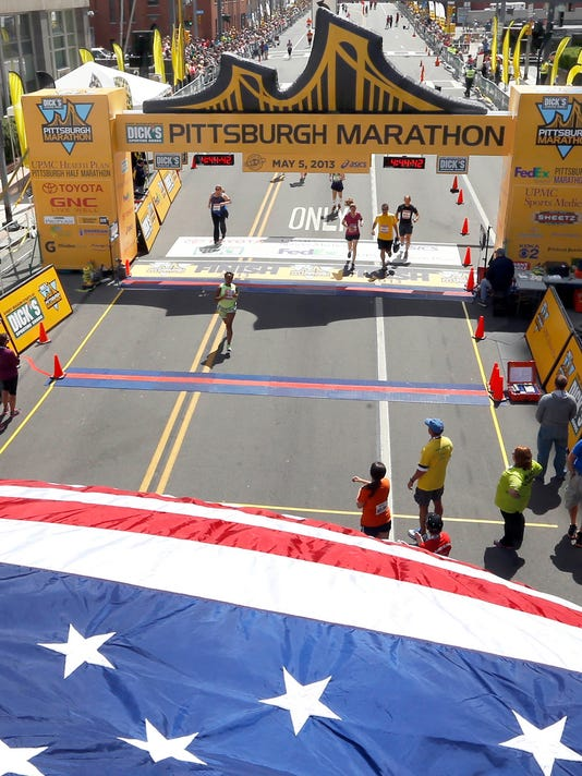 Runners pass through the finish line down the Boulevard of the Allies to complete the Pittsburgh Marathon on Sunday, May 5, 2013, in Pittsburgh. (AP Photo/Keith Srakocic)