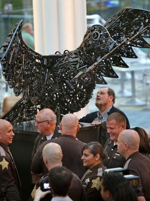 "People look at the ""Peace Dove"" sculpture after its unveiling Tuesday at Central Library."