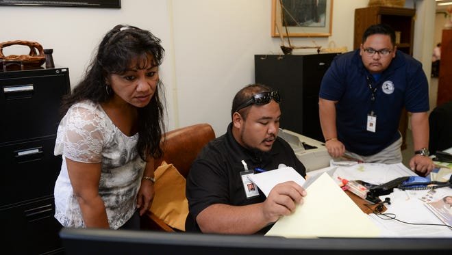 Guam Election Commission Program Coordinator Paciano F.N. Gumataotao, center, accepts Affadavit of Registration forms from volunteer voter registrar Grace Babauta, left, at the Guam Election Commission office in Hagatna on Feb. 22.