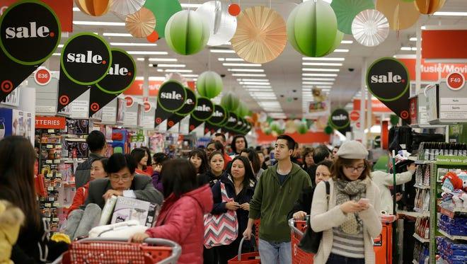 A crowd walks down an aisle at a Target Store.