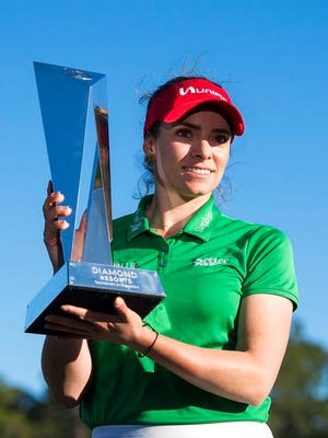Gaby Lopez holds the trophy after winning the Tournament of Champions LPGA golf tournament, Monday, Jan. 20, 2020, in Lake Buena Vista, Fla. Lopez ran in a 30-foot putt for birdie, to defeat Nasa Hataoka in a seven-hole playoff that took an extra day to finish after play was halted Sunday because of darkness.