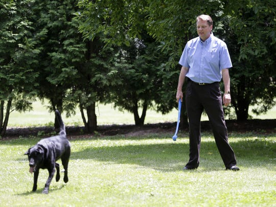 The Rev. Jay Fostner plays fetch with Abbey at St. Norbert College.