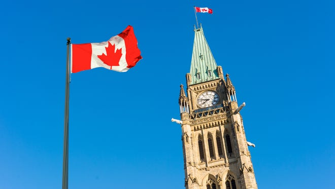 Peace Tower with a big Canadian flag over blue sky in Ottawa, Canada