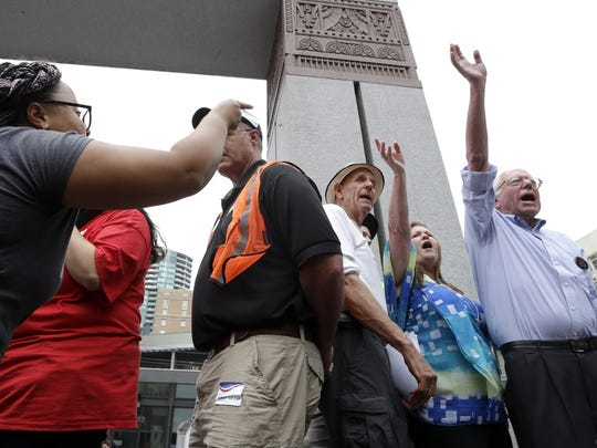 Marissa Johnson, left, points and yells as Democratic presidential candidate Sen. Bernie Sanders, I-Vt., waves before leaving the stage at a rally Saturday in downtown Seattle. Johnson and another co-founder of the Seattle chapter of Black Lives Matter took over the microphone just after Sanders began to speak and refused to relinquish it. Sanders eventually left the stage without speaking further and instead waded into the crowd to greet supporters.