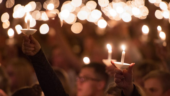 People holds candles in the air during a Christmas Eve service at Timberline Church Saturday, December 24, 2016.