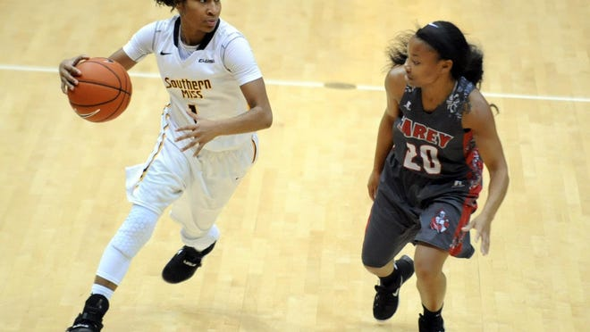 Southern Miss player Tajanay Veiga (1) dribbles past William Carey University's Jacquonna Young (20) in Reed Green Coliseum Monday, Dec. 28, 2015.