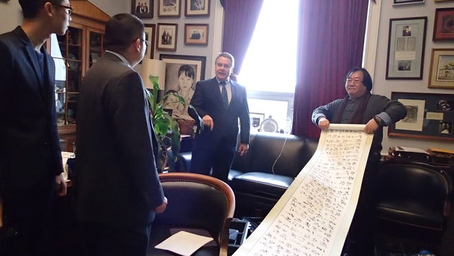 Rep. Chris Smith, center, is presented in his office with a poem by a group of Chinese dissidents who survived the Tiananmen Square massacre in 1989 and went on to lead activist organizations.