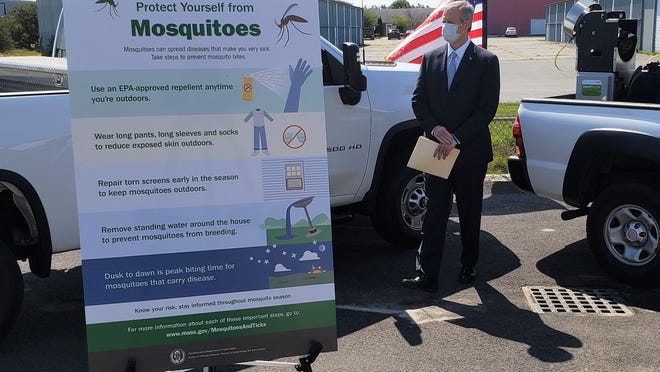 A masked Gov. Charlie Baker waits to talk about EEE at the Plymouth County Mosquito Control Project.