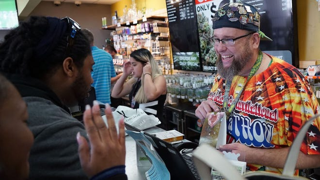 """""""Budtender"""" Jason Coleman describes the effects of a marijuana-infused lubricant to customers inside the Medicine Man cannabis dispensary in Denver on April 19, 2017. Thousands of marijuana tourists annually visit Denver — and stock up in stores such as Medicine Man — for the annual 420 celebration."""