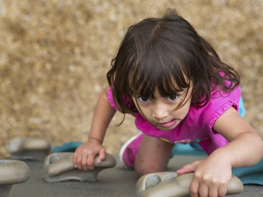 Maya Mohd Sani, 3, of Pittsford climbs a rock wall