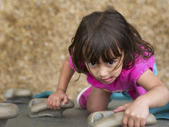 Maya Mohd Sani, 3, of Pittsford climbs a rock wall on the playground at Abraham Lincoln Park on July 15, 2015.