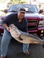 Dan Russo of Allenhurst and an Asbury Park Fishing Club member holds the 40.8-pound striped bass he caught.
