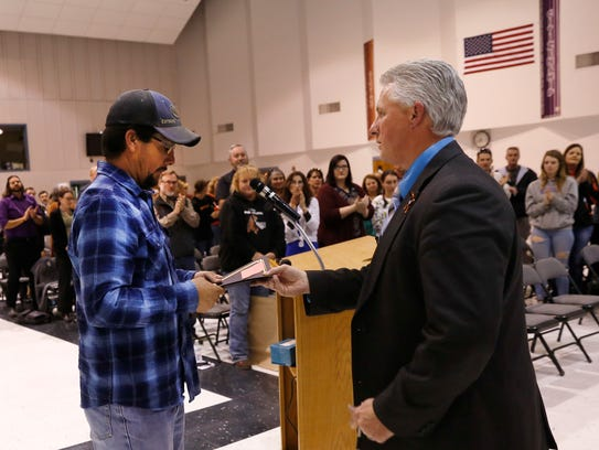 Maintenance employee Ritchie Chavez, left, shakes hands with Aztec Municipal School District Superintendent Kirk Carpenter during a school board meeting on Tuesday at Aztec High School.
