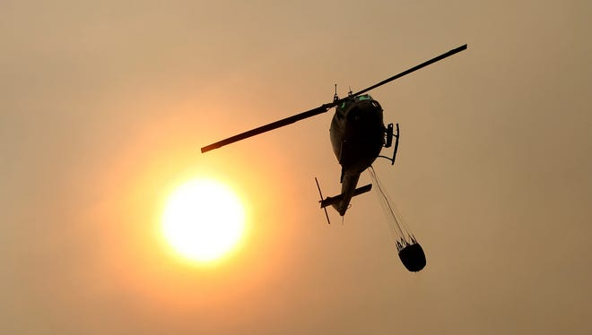 In this file photo, a Cal Fire helicopter flies over a California wildfire. Thursday, July 27, a firefighter killed by a wildfire in Alturas, California was scouting the area when he became trapped by the wind-stoked blaze, officials said Saturday. (AP Photo/Nic Coury)