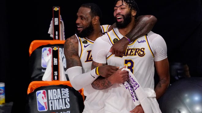 Los Angeles Lakers' LeBron James (23) and Anthony Davis (3) celebrate after the Lakers defeated the Miami Heat 106-93 in Game 6 of basketball's NBA Finals Sunday, Oct. 11, 2020, in Lake Buena Vista, Fla.