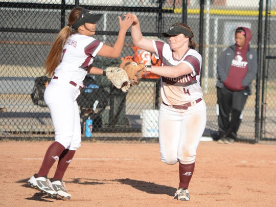 McMurry second baseman Megyn Castillo, left, congratulations Avery McDaniel after the shortstop's diving catch during Game 1 of a season-opening doubleheader against Trinity on Friday at Redbud Park.