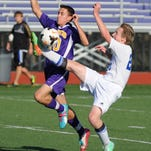 Unioto's Hudson Park battles Warren's Ben Koch for control of the ball in the first half of Saturday's district final at Logan High School.