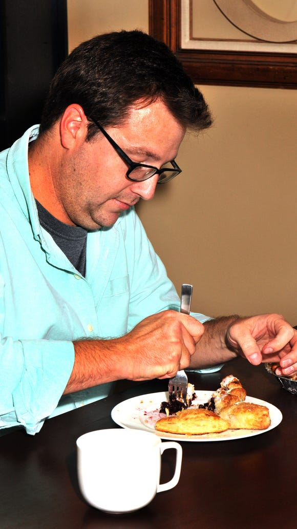 Korey Champagne, owner of Acadian Slice, samples his apple-bacon hand pie.