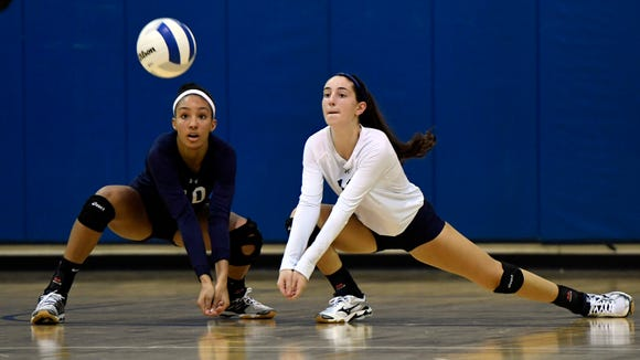 IHA outside hitter Sydney Taylor, left, and libero Erica Timpanaro, right, go for a dig.