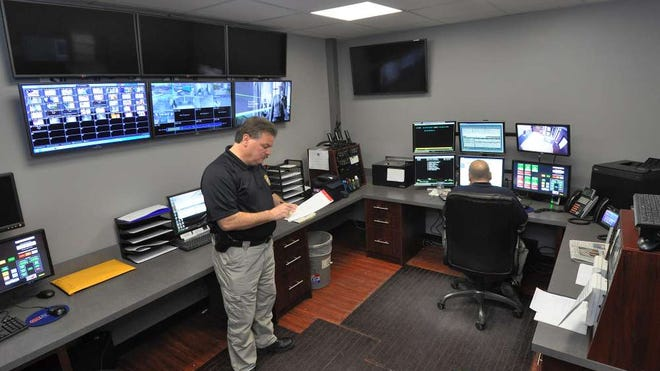 Woodland Park Police Chief Anthony Galietti works in the new state-of-the-art dispatch center at the station. Instead of a large clear glass window the station once had, individuals wanting to speak to police when they enter the building will pick up a phone where the person will be on two-way video. A woman uses the two-way system to communicate with a dispatcher.