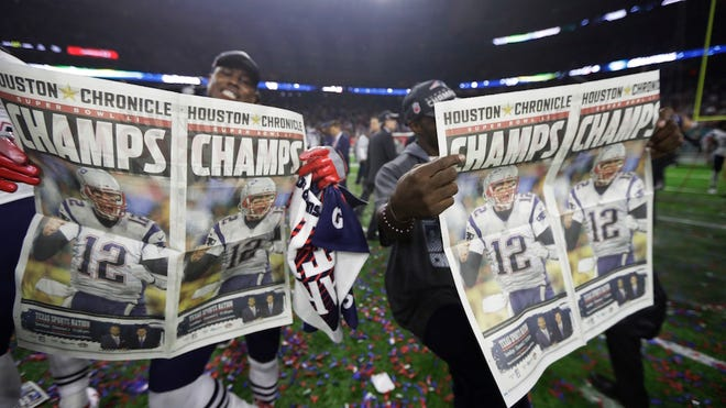 New England Patriots players celebrate with newspapers after their overtime win in the NFL Super Bowl 51 football game against the Atlanta Falcons, Sunday, Feb. 5, 2017, in Houston. (AP Photo/Tony Gutierrez)