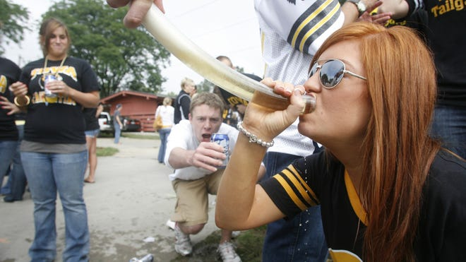 University of Iowa student Caryn Vaneck drinks from a beer bong while tailgating before a football game in Iowa City, Iowa.