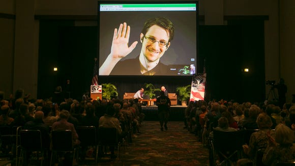 NSA leaker Edward Snowden appears on a live video feed broadcast from Moscow at an event sponsored by the ACLU Hawaii in Honolulu on Saturday, Feb. 14, 2015. (AP Photo/Marco Garcia)