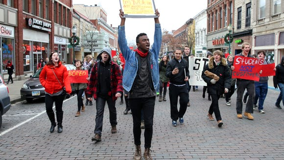 Ohio University senior Ryant Taylor leads a group of students in protesting the guaranteed tuition hike, as voted on by the university's Board of Trustees, that will raise the tuition costs of incoming freshman by 5% on Court Street on Thursday, Jan. 22, 2015. Protestors began outside the first floor of Baker University Center and then blocked traffic on Court Street and College Street. They ended their protests at the Civil War monument after police asked them to leave the street or be arrested.