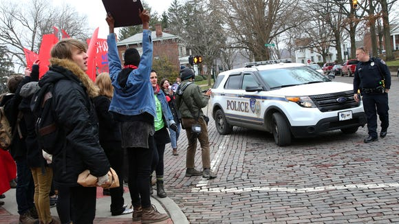 Ohio University students are asked to get off College Street by police as they protest the guaranteed tuition hike, as voted on by the university's Board of Trustees, that will raise the tuition costs of incoming freshman by 5% on Thursday, Jan. 22, 2015. Protestors began outside the first floor of Baker University Center and then blocked traffic on Court Street and College Street. They ended their protests at the Civil War monument after police asked them to leave the street or be arrested.