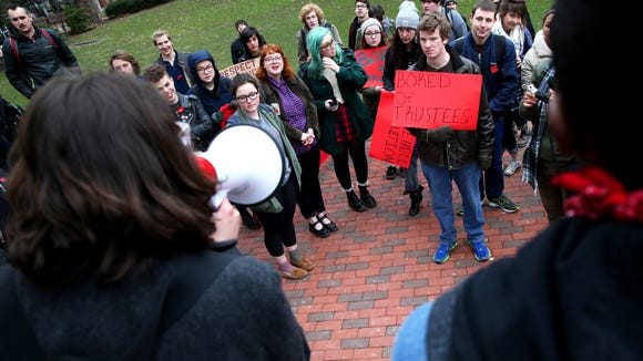 From left, Ohio University Student Senate president Megan Marzec and senior Ryant Taylor protest the guaranteed tuition hike, as voted on by the university's Board of Trustees, that will raise the tuition costs of incoming freshman by 5% at the Civil War monument on Thursday, Jan. 22, 2015. Protestors began outside the first floor of Baker University Center and then blocked traffic on Court Street and College Street.