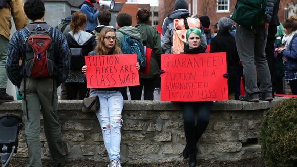 From left, Ellie Hamrick, an Ohio University alumna and Ohio University sophomore Taylor Baird, hold signs and protest the guaranteed tuition hike, as voted on by the university's Board of Trustees, that will raise the tuition costs of incoming freshman by 5% at the Civil War monument in Athens on Thursday, Jan. 22, 2015. Protestors began outside the first floor of Baker University Center and then blocked traffic on Court Street and College Street. They ended their protests at the Civil War monument after police asked them to leave the street or be arrested.