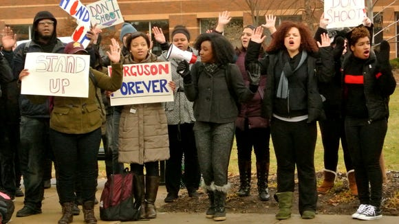 Portia Brown, junior, leads chanting with a megaphone, on the campus of Central Michigan University, Tuesday, November, 25, 2014.
