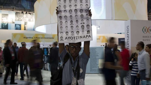 A man holds the portraits of the 43 missing students during a protest at the International Book Fair in Guadalajara, Mexico, on December 3, 2014.  (Hector Guerrero, AFP/Getty Images)