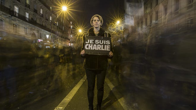 A woman pauses for a picture during a mass unity rally following the recent Paris terrorist attacks on January 11, 2015 in Paris, France.