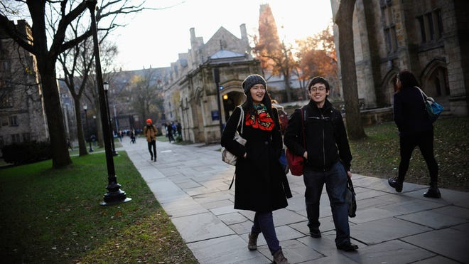 In this Nov. 20, 2014 photo, Yale University sophomore Yupei Guo, left, walks with friend Joseph Lachman on the school's campus in New Haven, Conn.