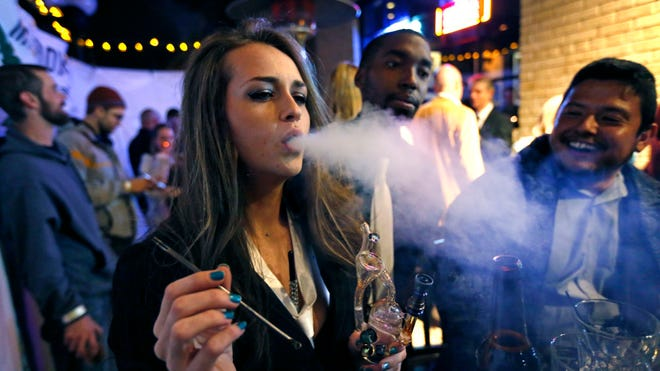 A woman smokes marijuana during a Prohibition-era themed New Year's Eve party at a bar in Denver.