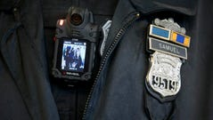 A Philadelphia Police officer demonstrates a body-worn camera being used as part of a pilot project in the department's 22nd District, Thursday, Dec. 11, 2014, in Philadelphia. (AP Photo/Matt Rourke)
