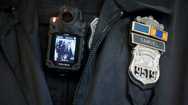 A Philadelphia Police officer demonstrates a body-worn camera being used as part of a pilot project in the department's 22nd District, Thursday, Dec. 11, 2014, in Philadelphia.