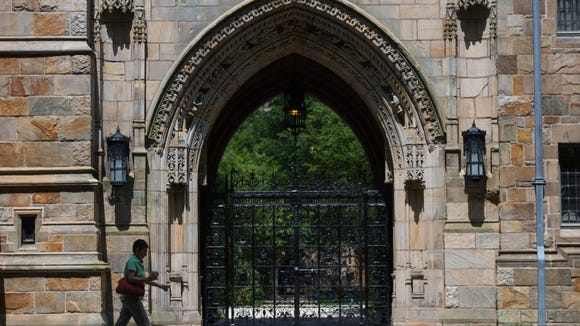 A pedestrian walks past Harkness Gate on the Yale University campus in New Haven, Connecticut, U.S., on Friday, June 12, 2015. (Craig Warga/Bloomberg)